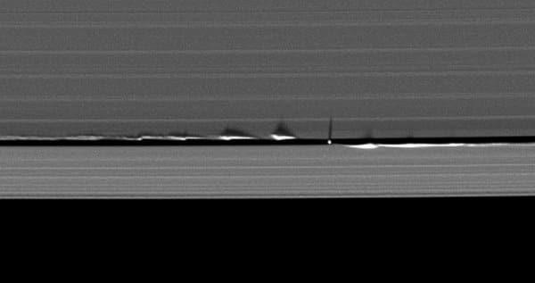 """ภาพของดวงจันทร์ Daphnis ที่ยานแคสสินีค้นพบเมื่อปี 2005 โดยพบอยู่ในช่องว่าง Keeler ของวงแหวน A การเคลื่อนที่ของมันทำให้วงแหวนสั่นเป็นระลอก และทอดเงาลงบนวงแหวนแถบอื่นๆ ทั้งนี้มีดวงจันทร์บริวารของดาวเสาร์หลายดวงที่อยู่ภายในช่องว่างของวงแหวนซึ่งมีอยู่มากมาย ทำหน้าที่เป็น """"คนเลี้ยงแกะ"""" คอยควบคุมรูปร่างของแถบวงแหวนไว้"""